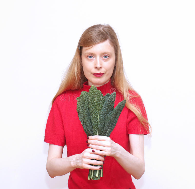 Holding kale leaves. Young blonde woman holding green kale leaves stock images
