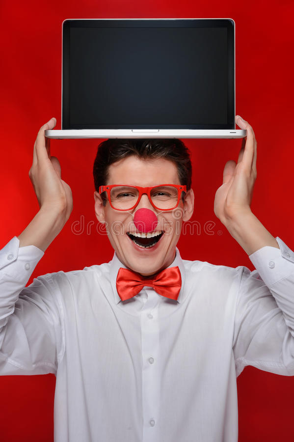 Holding laptop on his head. Cheerful man with clown holding a la stock images