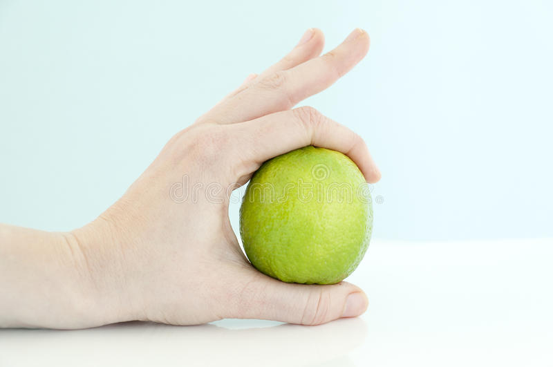 Holding a lime. A woman hand holding between the index finger and thumb a lime on a white table and a light blue background stock photo