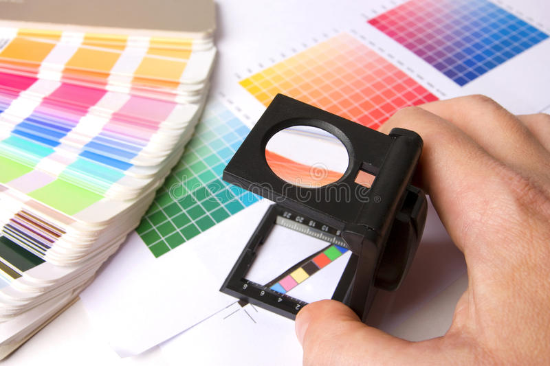 Holding a lupe and examing colours. Colour swatches of many colours and colour printing bars stock image