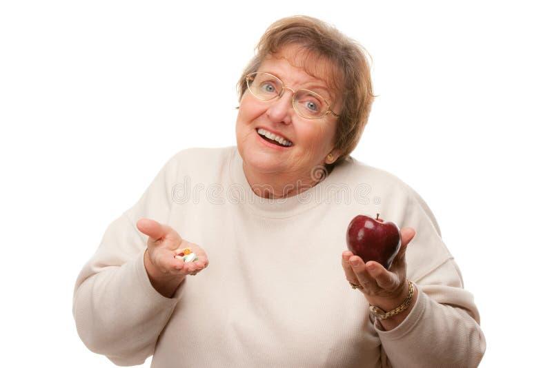Holding maggiore confusa Apple della donna e vitamine fotografie stock