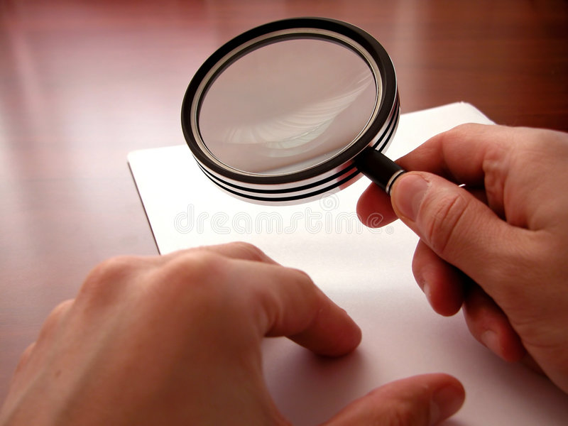 Holding a magnifying lens stock photos