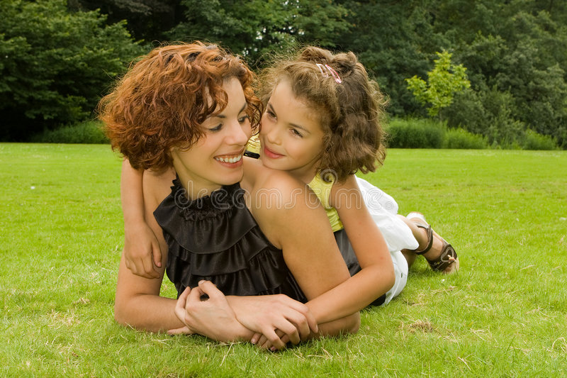 Holding mother. Little girl holding her beautiful mother in the park royalty free stock photos