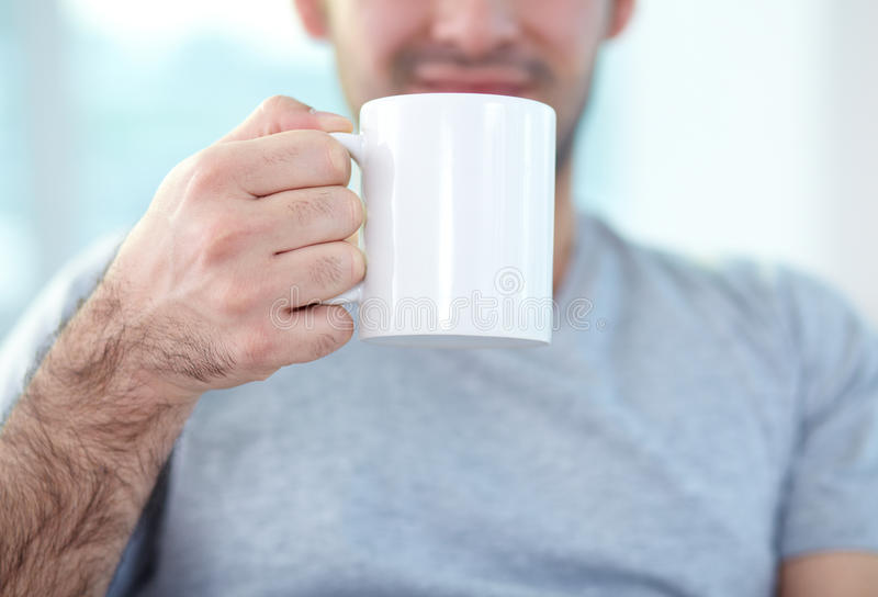 Holding mug. Close-up of male hand holding mug stock image