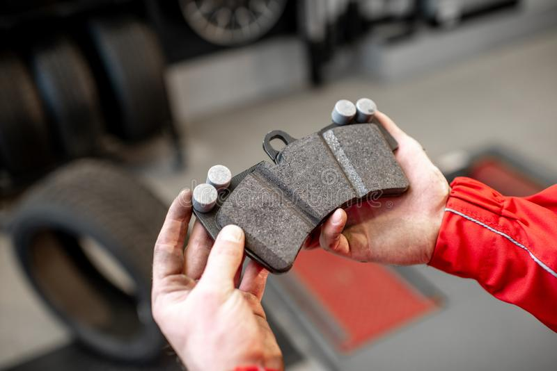 Holding new car brake pad. Auto mechanic holding new brake pad at the car service, close-up view stock image