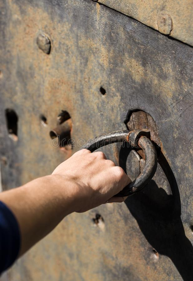 Holding old door metal ring. Holding old door metal ring with a hand royalty free stock photography