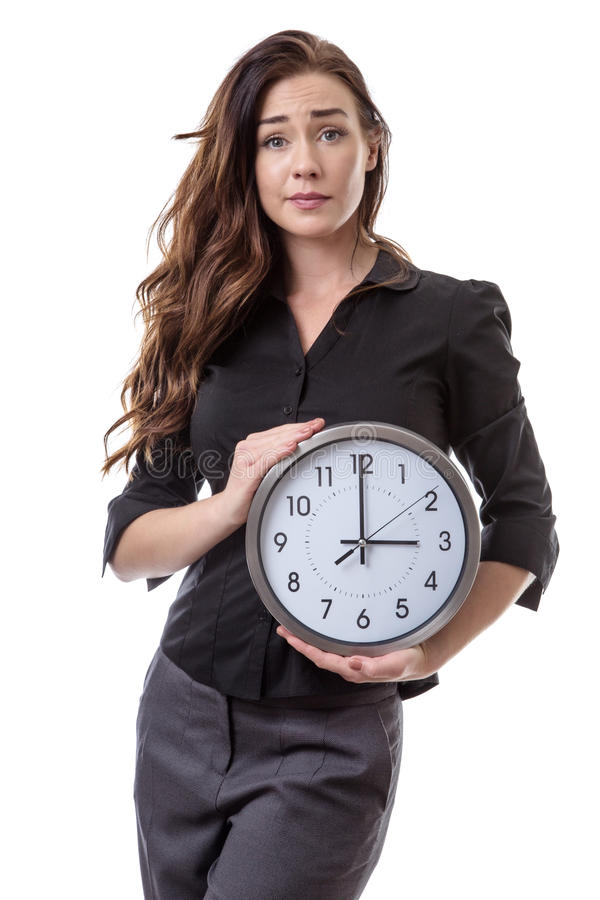 Holding onto time. Woman in a suit holding a large clock looking a little bit worried stock photography