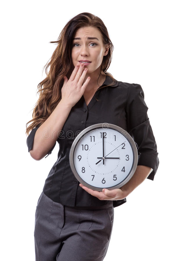 Holding onto time. Woman in a suit holding a large clock looking a little bit worried royalty free stock photos