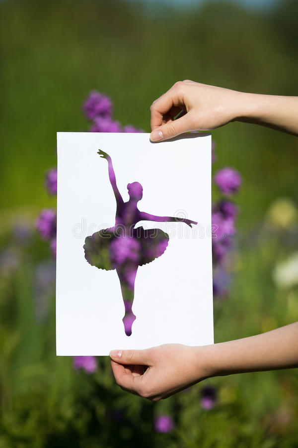 Holding papercut miniature ballerina over blooming flowers royalty free stock photography