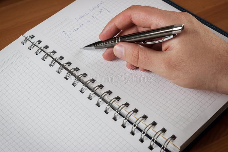 Man holding a grey pen on notebook and studying math royalty free stock image