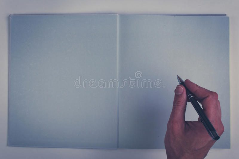 Holding pencil over blank page of a empty book. Hand writing in empty book - holding pencil over blank page of a empty book royalty free stock photography