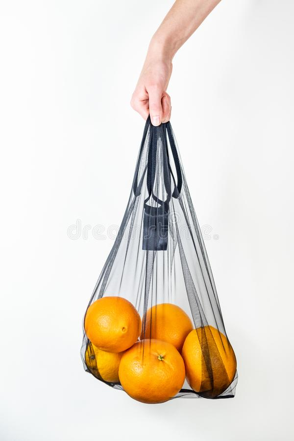 Holding a reusable string bag full of oranges stock images
