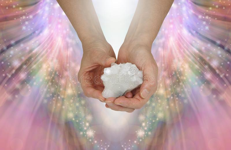 Holding a Sacred Cross Crystal Specimen. Female hands holding an Apothylite quartz cluster showing a very rare Crucifix detail on an angelic multicoloured royalty free stock photo
