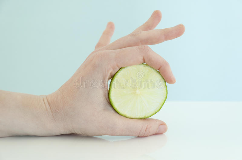Holding a slice of lime. A woman hand holding between the index finger and thumb a slice of lime on a white table and a light blue background stock images