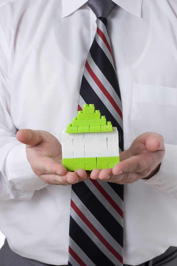 Holding small house. Businessman holding small green house stock images