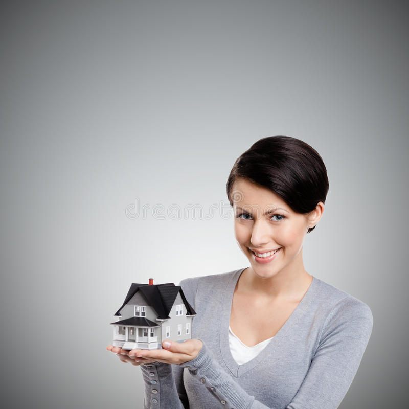 Holding small toy house. Young woman hands small toy house, isolated on grey stock image