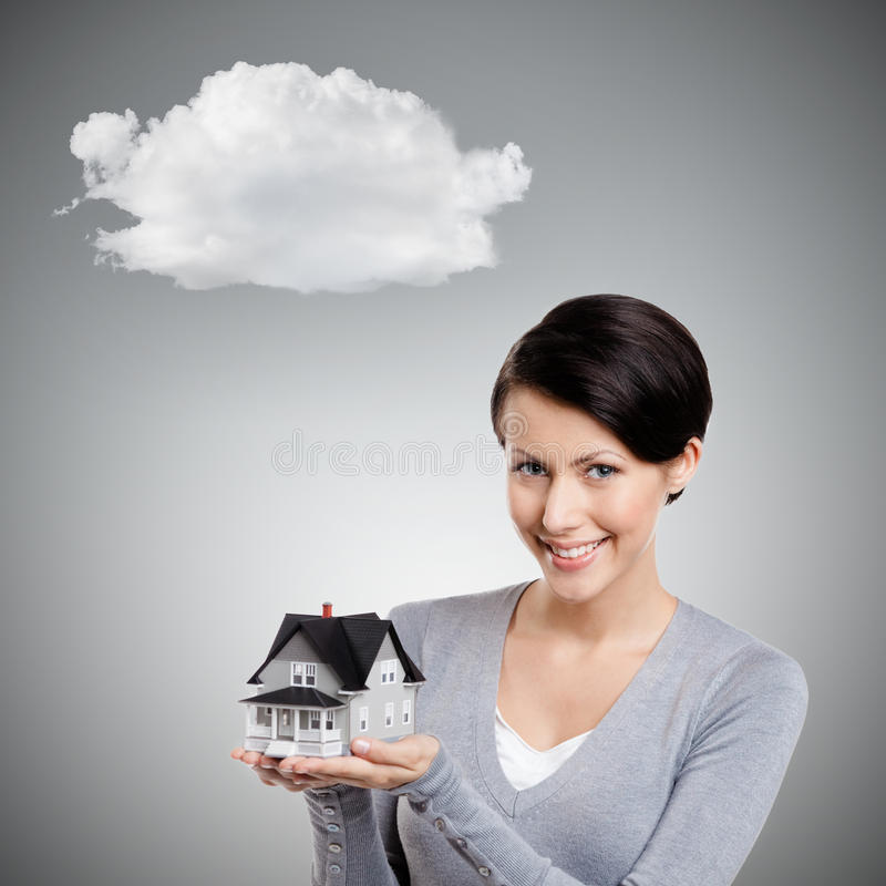 Holding small toy house. Young woman hands small toy house, isolated on grey background with cloud royalty free stock image
