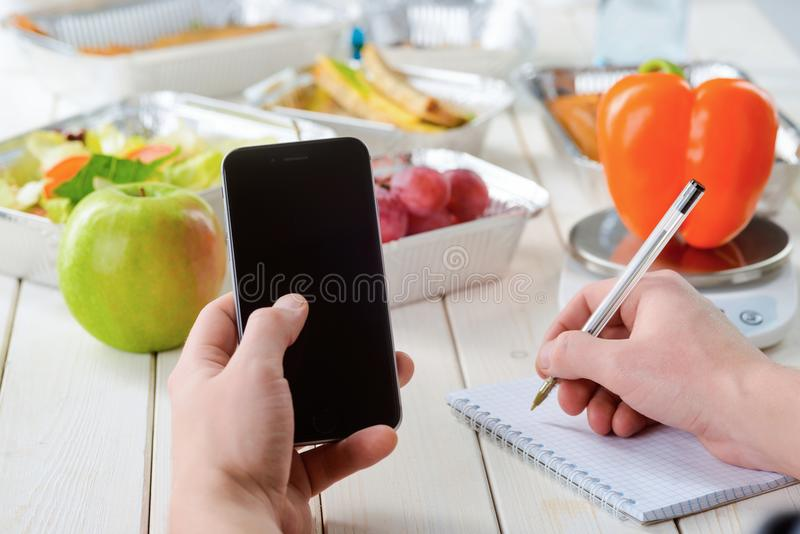 Making notes in kitchen. Holding a smartphone and making notes, close-up. Kitchen scale, a pepper, an apple, grapes and various dishes on the background, a light stock image
