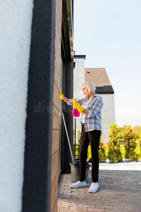 Elderly housewife wearing white sneakers holding sprinkler washing windows royalty free stock image
