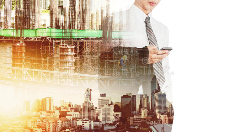A holding suit using smartphone with double exposure construction site and modern buildings in city sunrise royalty free stock image