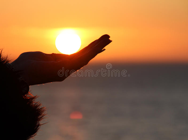 Holding sun in palm of hand. Photo of a woman holding the sun in the palm of her hand stock photos