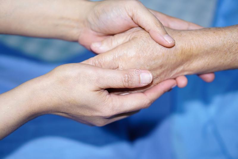 Holding Touching hands Asian senior or elderly old lady woman patient with love, care, helping, encourage and empathy. stock photo