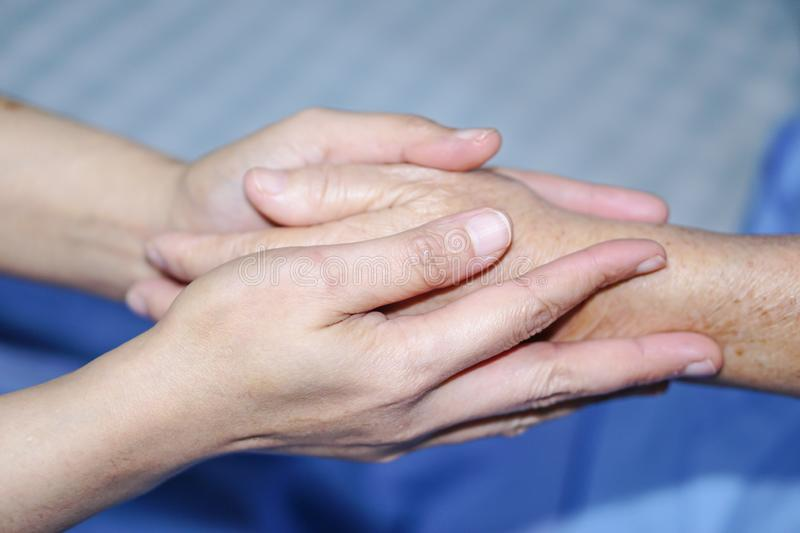 Holding Touching hands Asian senior or elderly old lady woman patient with love, care, helping, encourage and empathy. stock image