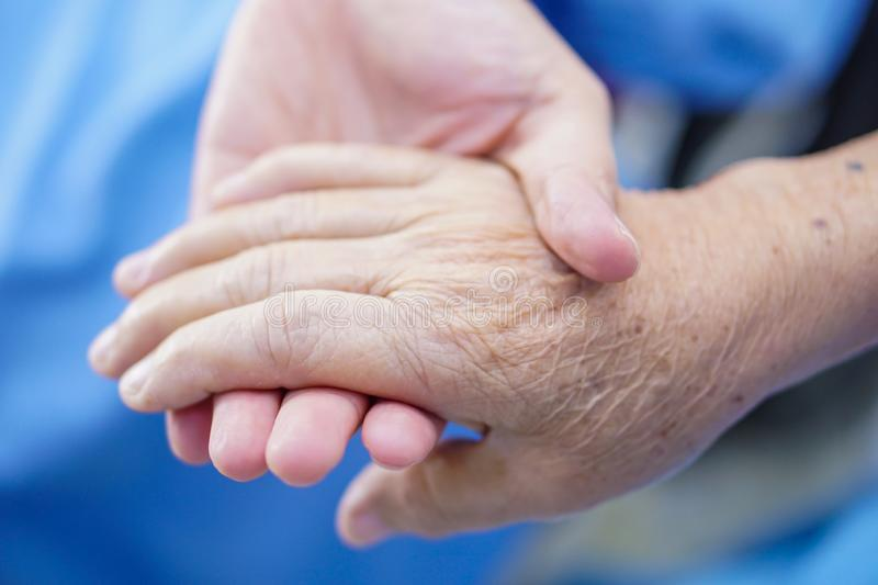 Holding Touching hands Asian senior or elderly old lady woman patient with love, care, helping, encourage and empathy. At nursing hospital ward : healthy strong royalty free stock photos