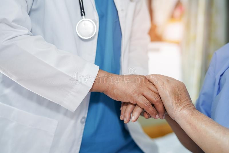 Holding Touching hands Asian senior or elderly old lady woman patient with love, care, helping, encourage and empathy. At nursing hospital ward : healthy strong royalty free stock image
