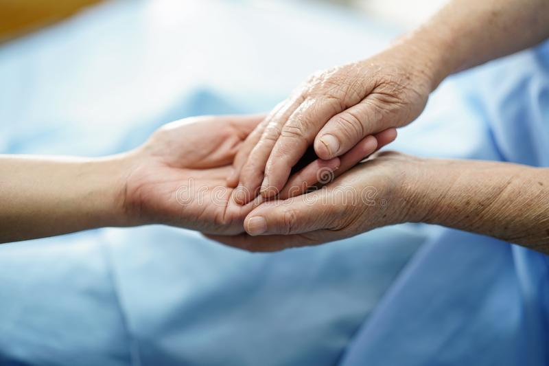 Holding Touching hands Asian senior or elderly old lady woman patient with love, care, helping, encourage and empathy at nursing h. Ospital ward : healthy strong royalty free stock image