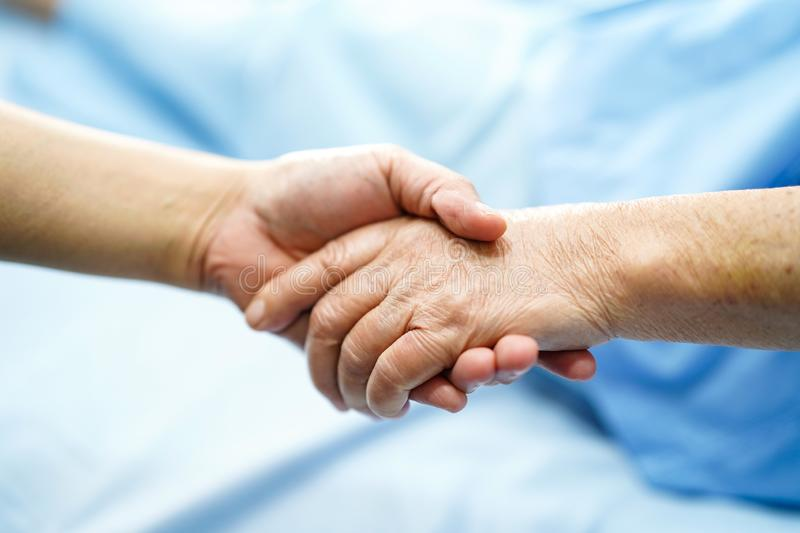 Holding Touching hands Asian senior or elderly old lady woman patient with love, care, helping, encourage. And empathy at nursing hospital ward : healthy strong royalty free stock photos