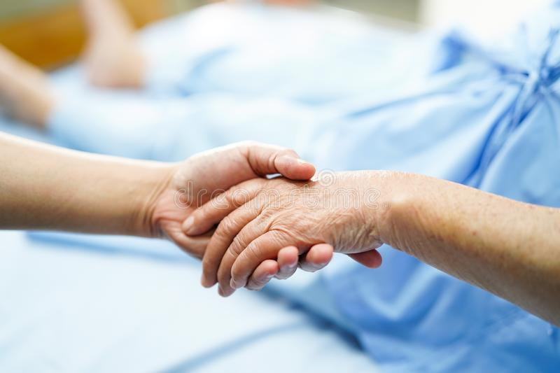 Holding Touching hands Asian senior or elderly old lady woman patient with love, care, helping, encourage and empathy. At nursing hospital ward : healthy strong stock images