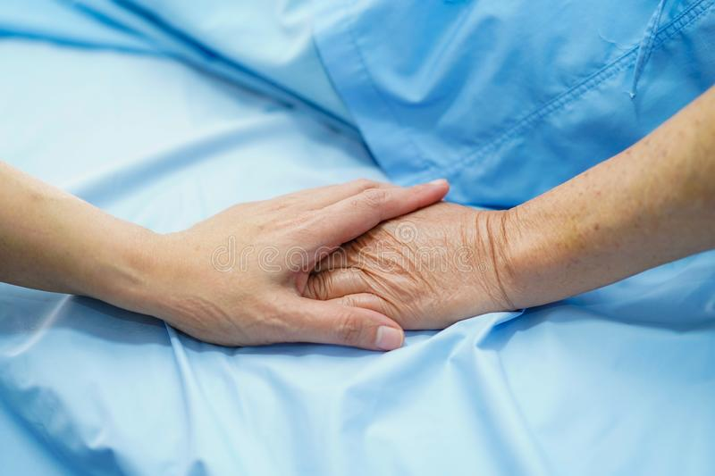 Holding Touching hands Asian senior or elderly old lady woman patient with love, care, helping, encourage and empathy at nursing h. Ospital ward : healthy strong royalty free stock photo