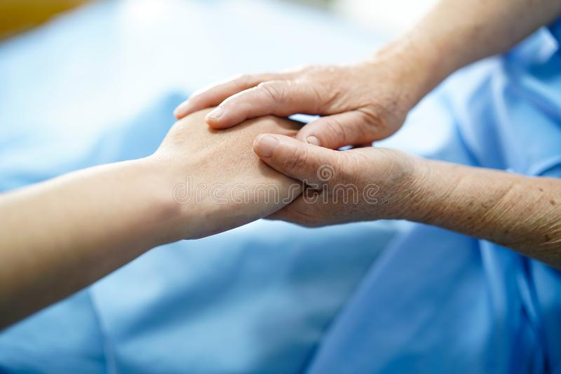 Holding Touching hands Asian senior or elderly old lady woman patient with love, care, helping, encourage and empathy at nursing h. Ospital ward : healthy strong royalty free stock photography