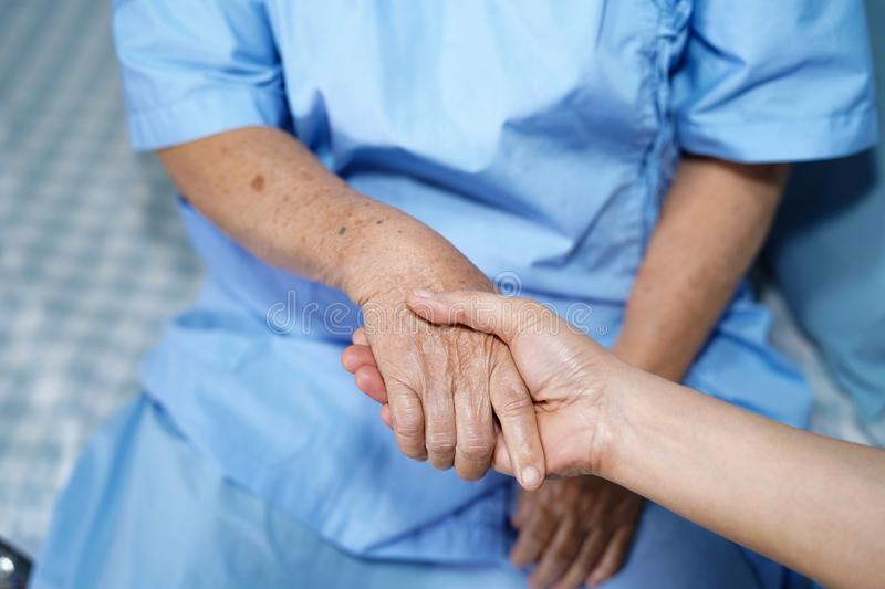 Holding Touching hands Asian senior or elderly old lady woman patient with love, care, helping, encourage and empathy at nursing h. Ospital ward : healthy strong royalty free stock images