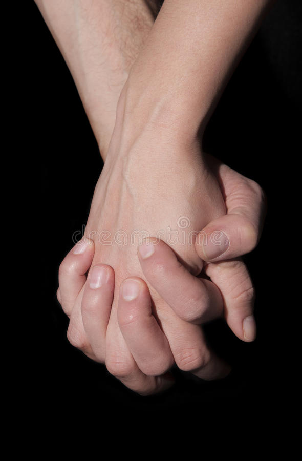 Holding two hands together. Union and love concept. Two hands holding each other. These are joined closely. Concept of help, love and marriage. On black royalty free stock photos