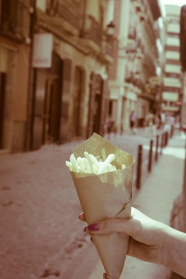 Holding typical fries in hand in the streets of old Europe stock photo