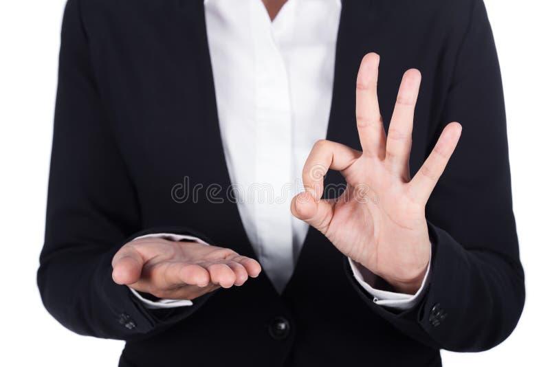 Holding van de bedrijfsvrouwen de open hand iets en tonend O.K. teken royalty-vrije stock afbeelding