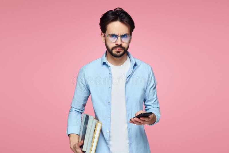 Holding van de Comnfident boekt de jonge gebaarde student en de mobiele telefoon, kijkt ernstig, terwijl status over roze achterg stock afbeeldingen