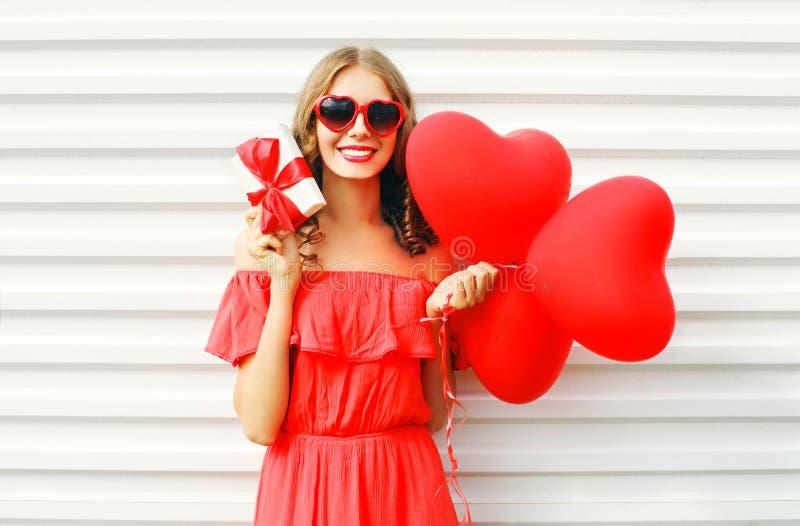 Holding van de portret de gelukkige glimlachende vrouw in de doos van de handengift en rode het hartvorm van luchtballons over wi stock afbeeldingen