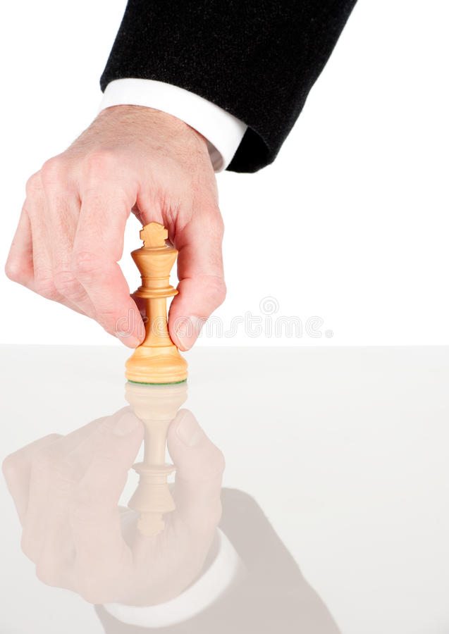 Holding a white king from chess game. Businessman hand holding a white king from chess game royalty free stock image
