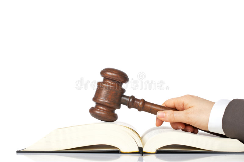 Holding a wooden gavel over the law book royalty free stock photos
