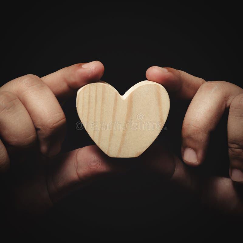 Holding wooden heart stock photos