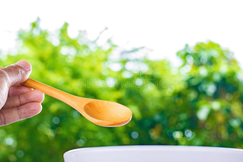 Holding wooden spoon on tree blurred background.Using food composition image.For food with candy and snacks image to package with stock photography