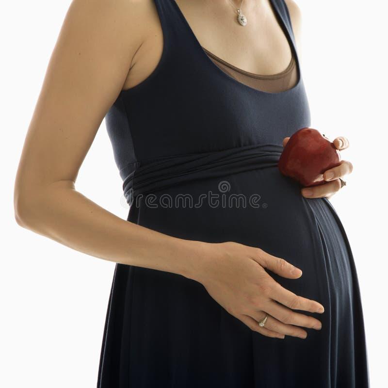 Holdingapfel der schwangeren Frau. stockbilder