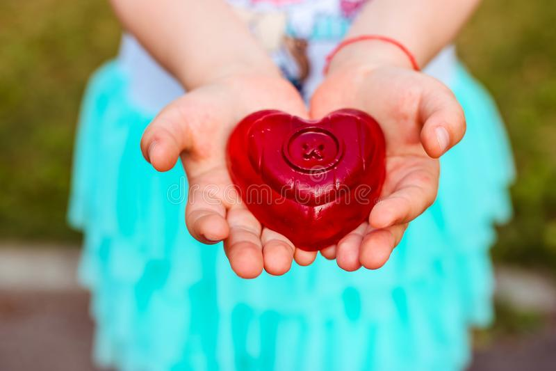 Holdingbabyseife des kleinen Mädchens in Form ein Herz in ihren Händen lizenzfreie stockbilder