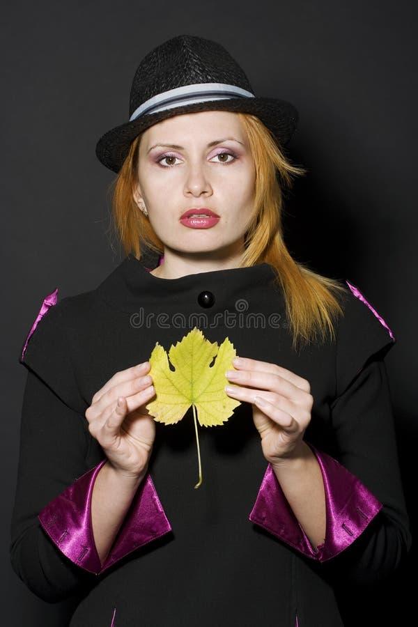 Holdingblatt der jungen Frau lizenzfreies stockbild