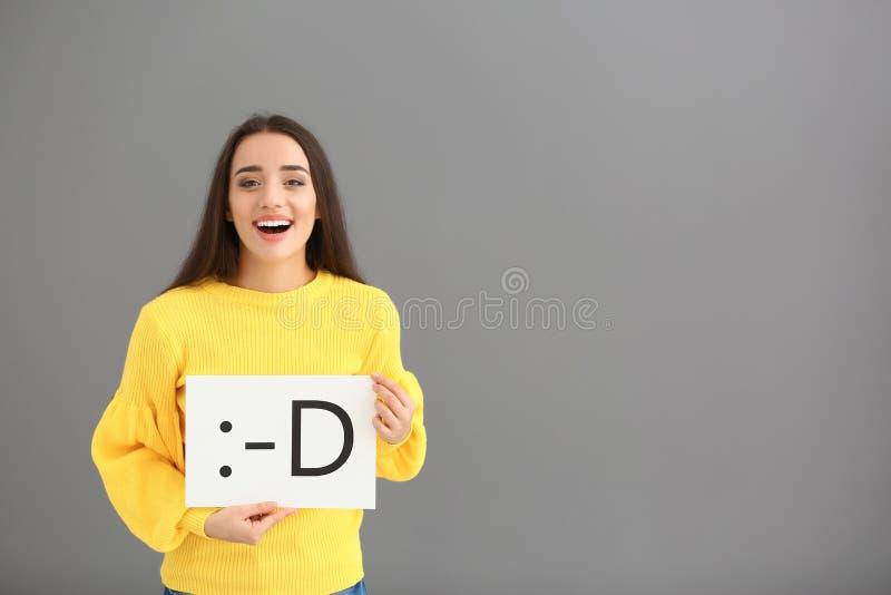 Holdingblatt papier der jungen Frau mit gezogenem Emoticon auf grauem Hintergrund lizenzfreies stockbild