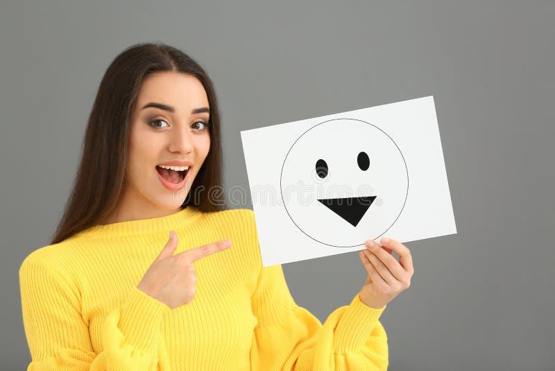 Holdingblatt papier der jungen Frau mit gezogenem Emoticon auf grauem Hintergrund lizenzfreie stockfotos