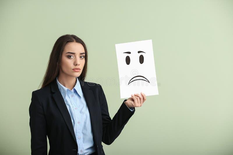 Holdingblatt papier der jungen Frau mit gezogenem Emoticon auf hellem Hintergrund lizenzfreies stockfoto